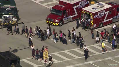 Students are evacuated from Marjory Stoneman Douglas High School during a shooting incident in Parkland, Florida, Feb. 14, 2018 in a still image from video.