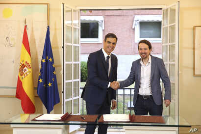 Spain's Prime Minister Pedro Sanchez, center, shakes hands with the leader of the Podemos party, Pablo Iglesias, at the Moncloa Palace in Madrid, Oct. 11, 2018.