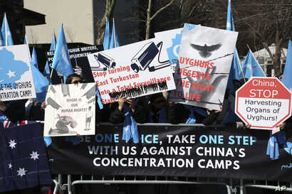Uighurs and their supporters rally across the street from United Nations headquarters in New York, Thursday, March 15, 2018. Members of the Uighur Muslim ethnic group held demonstrations in cities around the world on Thursday to protest a sweeping Ch