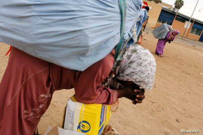 FILE - A Moroccan woman rests as she carries goods to be taken across the border from Spain's North African enclave of Melilla into Moroccan settlement of Beni Ansar, in Melilla, Spain, July 19, 2017.