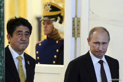FILE - Russia's President Vladimir Putin (R) and Japan's Prime Minister Shinzo Abe are seen walking following talks at the Kremlin in Moscow April 29, 2013.