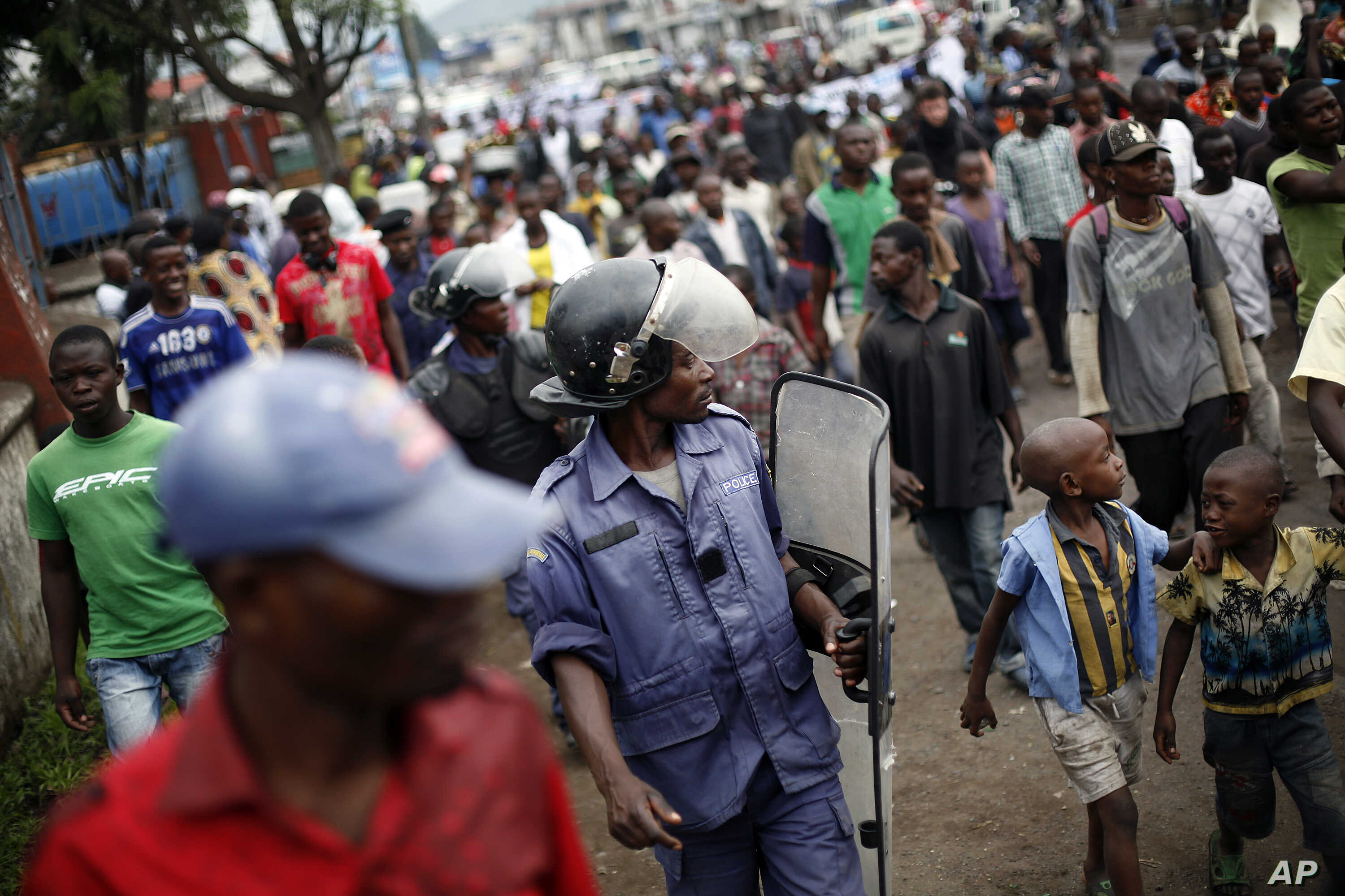 Congolese policeman in riot gear keeps an eye on Goma residents, including street children, who gathered for an anti-Kabila demonstration supported by the M23 rebel movement in Goma, DRC, November 28, 2012.