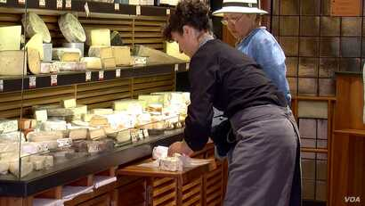 Wrapping up cheese at Androuet, one of France's leading cheese stores. (L. Bryant/VOA)