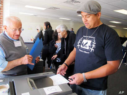 In this Oct. 26, 2012, photo, Dashiell Beardsley of the Laguna Pueblo, right, feeds his ballot into a voting machine during early voting in Albuquerque, N.M.