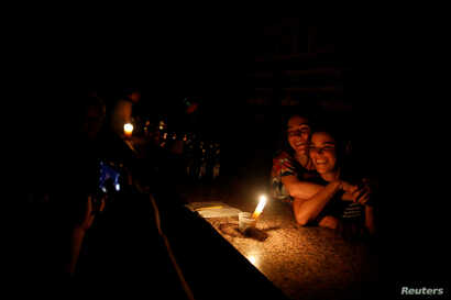 People pose for a picture at a bar during a blackout in Caracas, Venezuela, March 29, 2019.