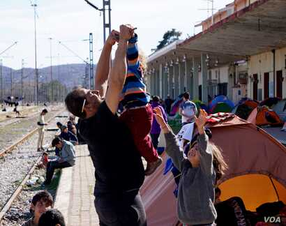 A Syrian father plays with his son. (Jamie Dettmer for VOA)