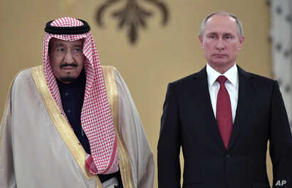 FILE - In this Oct. 5, 2017 file photo, Russian President Vladimir Putin, right, and Saudi Arabia's King Salman pose for a photo during a welcoming ceremony in Moscow.