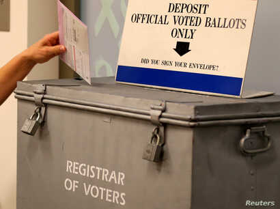 A ballot is placed into a locked ballot box by a poll worker as people line-up to vote early at the San Diego County Elections Office in San Diego, California, US, Nov. 7, 2016.