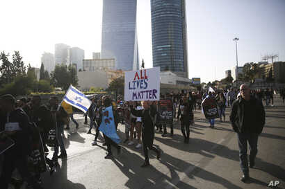 People march as they protest against Israeli police and demand the appointment of an investigating judge to probe the killing of Yehuda Biadga, a mentally ill Ethiopian-Israeli, by Israeli police, in Tel Aviv, Israel, Wednesday, Jan. 30, 2019.