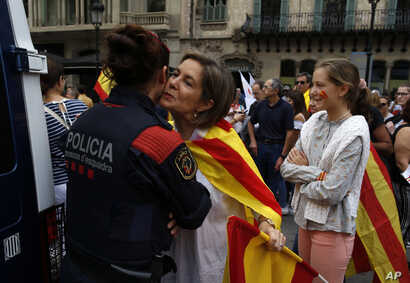 "A woman wearing the Spanish and Catalonian colors greets a Catalan Mossos d'Esquadra regional police officer as people celebrate a holiday known as ""Dia de la Hispanidad"" or Spain's National Day in Barcelona, Oct. 12, 2017."