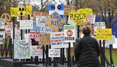A visitor watches protest banners outside the UN Climate Change Conference in Bonn, Germany, Nov. 6, 2017.