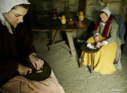 FILE – Reactors dressed as Pilgrims prepare a meal at Plimoth Plantation in Plymouth, Massachusetts in this 2004 file photo.