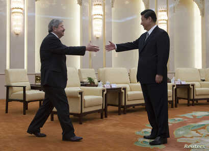 FILE - Iowa Governor Terry Branstad, left, reaches out to shake hands with Chinese President Xi Jinping before a meeting at the Great Hall of the People in Beijing, April 15, 2013.