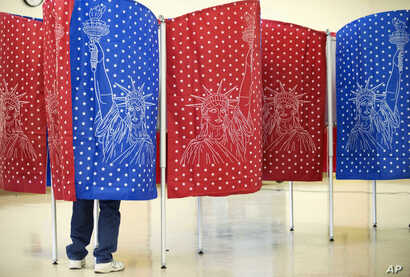 A voter marks a ballot for the New Hampshire primary inside a voting booth at a polling place, Feb. 9, 2016, in Manchester, N.H.