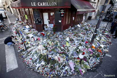 """People mourn outside """"Le Carillon"""" restaurant a week after a series of deadly attacks in Paris, Nov. 22, 2015."""