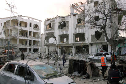Somali soldiers walk past a destroyed building in Mogadishu, Somalia, March 1, 2019.
