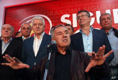 FILE - Milo Djukanovic, center, then the prime minister of Montenegro, speaks in his headquarters in Podgorica, Oct. 17, 2016. A Montenegrin court this year confirmed prosecution indictments against 14 people for masterminding a coup attempt in Monte...