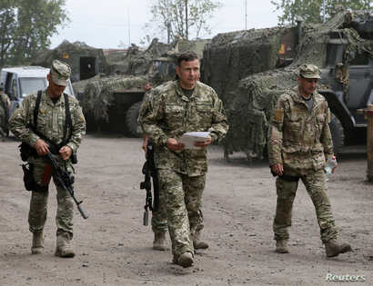 Newly appointed Ukrainian Defense Minister Valery Heletey, center, walks with troops at a temporary base near the city of Slovyansk, July 6, 2014.