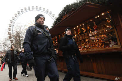 Police officers patrol a Christmas market near the city hall in Berlin, Wednesday, Dec. 21, 2016