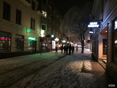 Despite police warnings that women should not go out alone at night for safety, groups of party goers slide in the snow from restaurants to bars to clubs late into Saturday night as the night walkers patrol, Ostersund, Sweden, March 19, 2016. (Heathe...