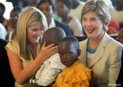 FILE - United States first lady Laura Bush and daughter Jenna, left, hold Rwandan children they met at an AIDS project during a church service at Kagarama Church in Kigali, July 14, 2005. Bush was on the last leg of her official visit to Africa after...