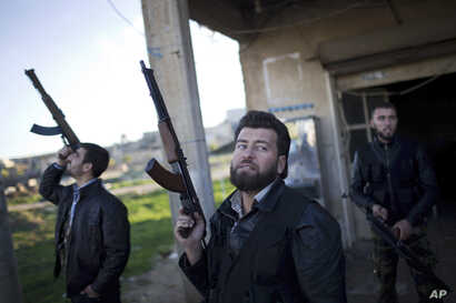 FILE - Free Syrian Army fighters look at a Syrian Army jet, not pictured, in Fafeen village, north of Aleppo province, Syria.
