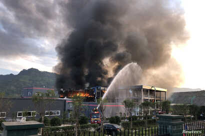 FILE - Rescue workers try to put out a fire after an explosion at a chemical plant inside an industrial park in Yibin, Sichuan province, China July 12, 2018.