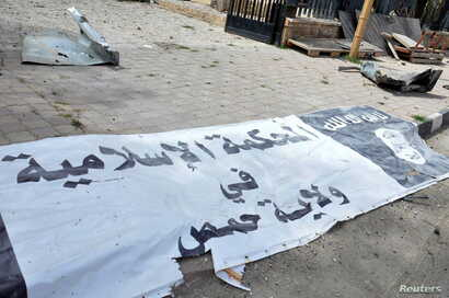 A banner belonging to the Islamic court of the Islamic State is seen on the ground after forces loyal to Syria's President Bashar al-Assad recaptured Palmyra city in this handout picture provided by SANA on March 27, 2016.