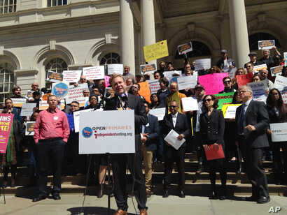 FILE - In this April 14, 2016, an acctivist speaks at a rally on the steps of New York's City Hall. As New York voters prepared for presidential primary elections, critics decried restrictive ballot rules that they say disenfranchise millions of New ...