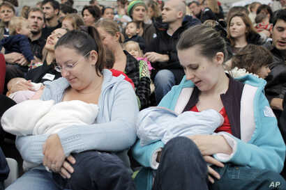 FILE - Mothers breast-feed their babies in Paris, Oct. 11, 2008, during a worldwide breast-feeding event.