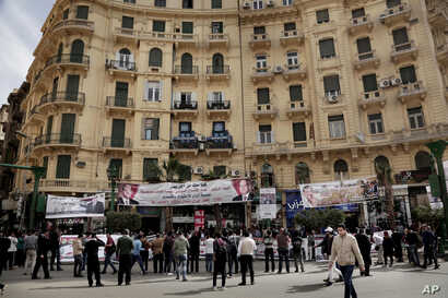 FILE - People hold banners showing support for Egyptian presidential candidate Moussa Mustafa Moussa on a street in downtown Cairo, March 4, 2018.