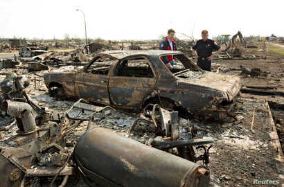 Canadian Prime Minister Justin Trudeau and Fort McMurray Fire Chief Darby Allen, right, look over a burnt out car while visiting neighborhoods devastated by the wildfire that forced the evacuation of the city in Fort McMurray, Alberta, Canada, May 13...