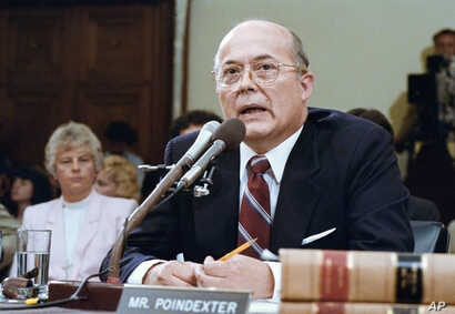 Former National Security Advisor John Poindexter, contradicting President Reagan, tells Iran-Contra committees in Washington on Wednesday, July 15, 1987 that the President initially approved selling arms to Iran in late 1985 in a straight-arms for ho...