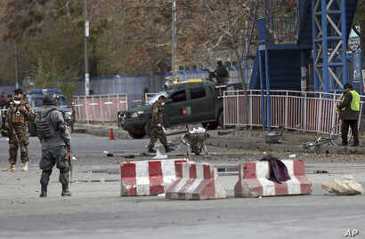 Security forces inspect the site of a deadly blast in the center of Kabul, Afghanistan, Nov. 12, 2018.