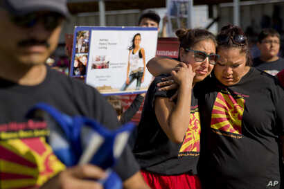 Jenna Loring, left, the aunt of Ashley HeavyRunner Loring, cries with her cousin, Lissa Loring, during a traditional blanket dance before the crowd at the North American Indian Days celebration on the Blackfeet Indian Reservation in Browning, Mont., ...