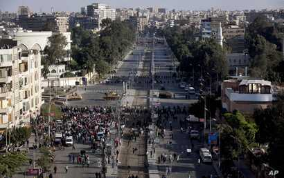 Egyptian army tanks secure the perimeter of the presidential palace while protesters gather chanting anti-President Mohamed Morsi slogans, Cairo, Egypt, December 7, 2012.