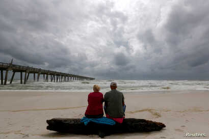 A local couple, who asked not to be named, watch waves come ashore in advance of  Hurricane Michael in Pensacola, Florida, Oct. 9, 2018.