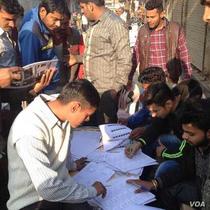 Voters in Ghaziabad in the battleground Uttar Pradesh state who went to the polls Saturday to choose a regional government turn up early to search for their names in the voters list. (A. Pasricha/VOA)
