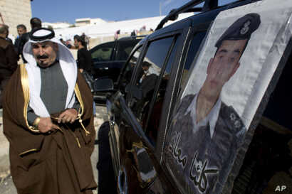 "A Jordanian man walks past a poster that is pasted on a vehicle with a picture of slain Jordanian pilot, Lt. Muath al-Kaseasbeh with Arabic that reads, ""we are all Muath,"" at his home village of Ai, near Karak, Jordan, Feb. 4, 2015."
