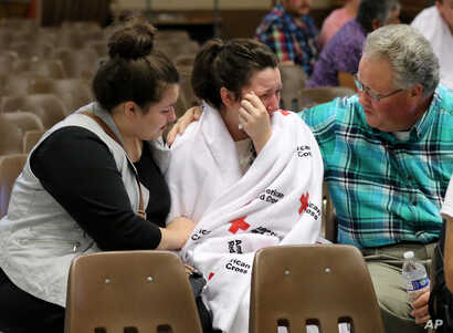 Hannah Miles, center, is reunited with her sister Hailey Miles, left, and father Gary Miles, right, after a shooting at Umpqua Community College in Roseburg, Oregon, Oct. 1, 2015.