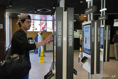 Brandon Alba from Milwaukee orders food at a self-service kiosk at a McDonald's restaurant in Chicago, June 1, 2017. The company that helped define fast food is making supersized efforts to reverse its fading popularity and catch up to a landscape th...
