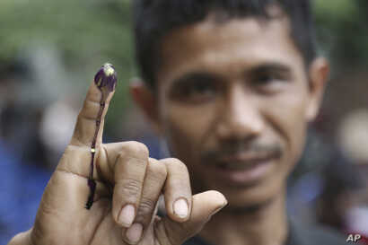 An Indonesian man shows his ink-stained finger after voting in Jakarta, Indonesia, Feb. 15, 2017.