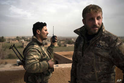 U.S.-backed Syrian Democratic Forces (SDF) fighters talk on a radio in a rooftop position as fight against Islamic State militants continues in the village of Baghouz, Syria, Feb. 16, 2019.