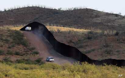 FILE - U.S. Border Patrol agents monitor the border fence in Naco, Ariz., Oct. 2, 2012. National Guard contingents in U.S. states that border Mexico say they are waiting for guidance from Washington to determine what they will do following President ...