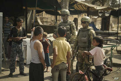 FILE - In this Sept. 15, 2017, photo, Russian soldiers escorting a group of journalists stand guard as children gather, in Deir ez-Zor, Syria.