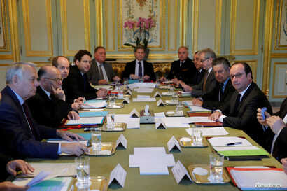 French President Francois Hollande (right) is surrounded by ministers and officials as they hold a defense council at the Elysee Palace in Paris, April 21, 2017.