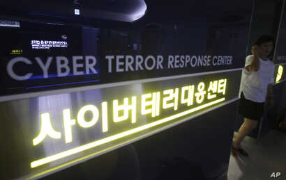 FILE - A woman walks by a sign at Cyber Terror Response Center of National Police Agency in Seoul, South Korea.