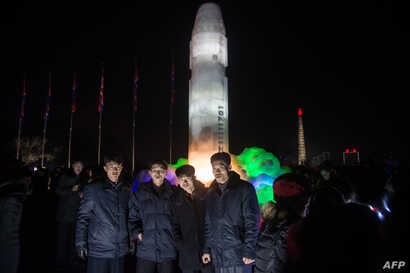 A group of men stand before an ice sculpture depicting a Hwasong-15 intercontinental ballistic missile at the Pyongyang Ice Sculpture Festival in Pyongyang on Dec. 31, 2017.