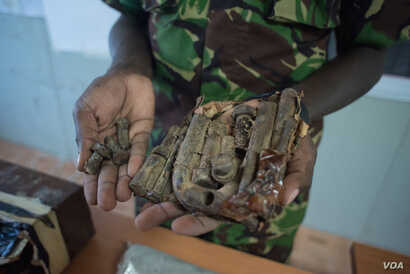 AMISOM IED expert Hollypass Lagat holds bolts found inside IEDs which were defused before being set off, Sept. 21, 2016. (Photo: J. Patinkin/VOA)
