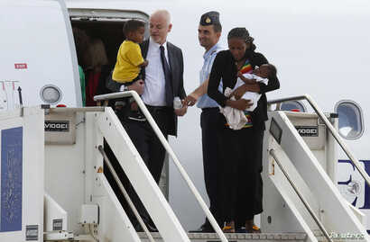 Italy's vice minister for foreign affairs, Lapo Pistelli, left, greets Mariam Yahya Ibrahim and her family arriving from Sudan in Rome July 24, 2014.